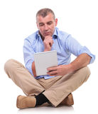 Casual old man sits and looks pensively at pad Stock Photo
