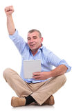Casual old man sits with pad and cheers Stock Images