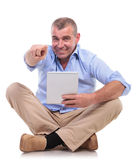 Casual old man sits with pad and points Royalty Free Stock Photo