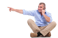 Casual old man sits and points while on phone Stock Photos
