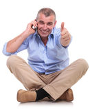 Casual old man sits and shows ok while on phone Royalty Free Stock Image