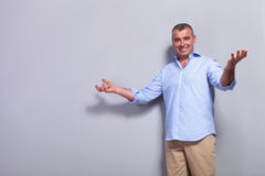 Casual old man welcomes you. Casual senior man welcoming you with a big smile. on gray background Stock Photo