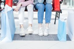 Casual outfits of girls in shopping mall. Close-up of unrecognizable teenage girls in sneakers sitting on bench and resting after purchases in stores of shopping Royalty Free Stock Photo