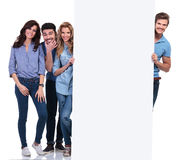 Casual people fooling around and presenting a blank board stock images