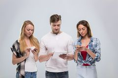 Casual People Group, Young Man Two Woman Happy Smile Using Cell Smart Phone Network Communication Royalty Free Stock Photos