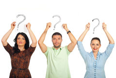 Casual people holding questions mark overhead. Three casual people standing in a line and holding questions marks over their heads isolated on white background stock photos