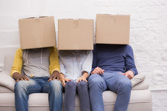 Casual people sitting on couch with boxes over heads Royalty Free Stock Photo
