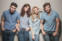 Casual people standing with hands in their pockets. Relaxed young casual people standing with hands in their pockets against gray wall Stock Image