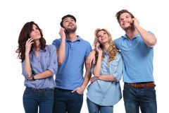 Casual people talking on phone and looking up to something. Group of casual people talking on phone and looking up to something on white background Stock Photography
