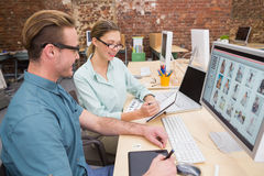 Casual photo editors using computer in office Stock Images