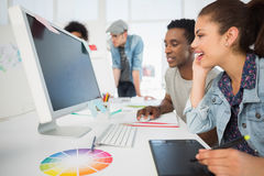 Casual photo editors using graphics tablet. Side view of casual photo editors using graphics tablet in the office Royalty Free Stock Image
