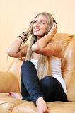 Casual portrait of a beautiful girl enjoying music and smiling. Sitting at sofa Stock Photo