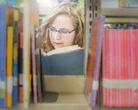 Casual Portrait of Girl in Library Reading a Book