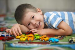 Casual portrait of the preschool boy playing with cars