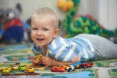 Casual portrait of a toddler playing with toy cars