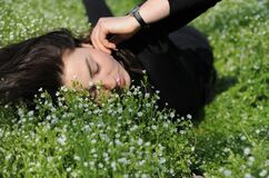 Casual portrait of a woman lies on the grass and listens to music on headphones