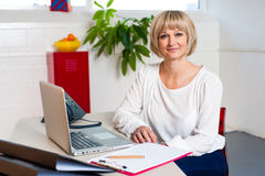 Casual portrait of a woman seated at her work place Stock Photos