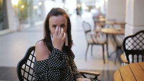 Portrait of a woman at a table on the street. Casual portrait of young tourist sitting at tables outdoors stock video