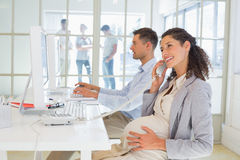 Casual pregnant businesswoman talking on phone at desk Royalty Free Stock Photo