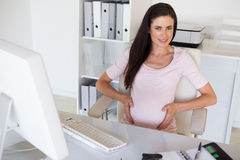 Casual pregnant businesswoman touching her bump at her desk smiling at camera Royalty Free Stock Photos