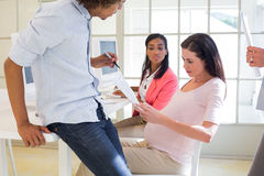 Casual pregnant businesswoman working with colleagues Stock Photo