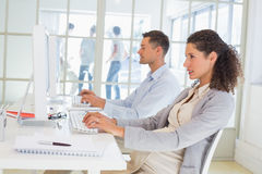 Casual pregnant businesswoman working at desk Stock Photos