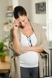 Casual pregnant woman at home. Blissful pensive pregnant woman at home. Casual professional female standing at leaving room stock photo