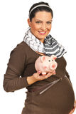Casual pregnant woman with piggy bank Stock Photo