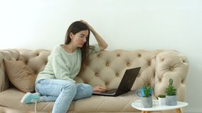 Casual pretty woman blogging on laptop at home stock video