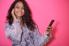 Casual pretty woman enjoy listening a music. Close up portrait of casual pretty woman enjoy listening a music on pink background Stock Images