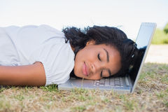 Casual pretty woman lying on the grass sleeping on her laptop Royalty Free Stock Photography