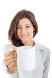 Casual pretty woman offered white cup of coffee or tea to you or royalty free stock photo