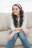 Casual pretty woman sitting on a cosy couch Stock Photo