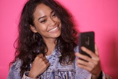 Casual pretty woman taking selfies using mobile phone camera. Close up portrait of casual pretty woman taking selfies using mobile phone camera on pink Stock Image