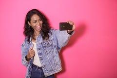 Casual pretty woman taking selfies using mobile phone camera. Portrait of casual pretty woman taking selfies using mobile phone camera on pink background Stock Photo