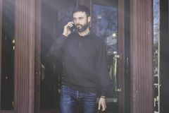 Casual professional entrepreneur using smart phone outside.Bearded Man in talking on a mobile phone. Stock Photography