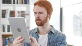 Casual Redhead Man Browsing on Tablet stock video