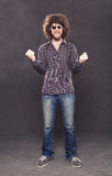 Casual satisfy. Young happy man with crisp hair and sunglasses standing  on grunge background Royalty Free Stock Photo