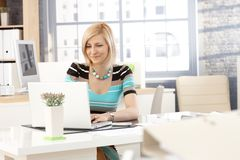 Casual secretary working with laptop computer Royalty Free Stock Image