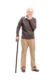 Casual senior with a black wooden cane. Full length portrait of a casual senior with a black wooden cane posing isolated on white background royalty free stock photo