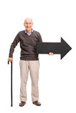 Casual senior with a cane holding a black arrow Stock Photography