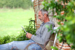 Casual senior man sitting in garden and using tablet. Mature man using tablet on a bench in countryside Stock Photos