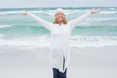 Casual senior woman with arms outstretched at beach Stock Image