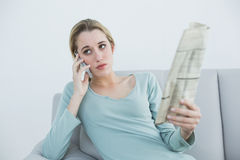 Casual serious woman phoning sitting on couch. Holding newspaper Stock Image