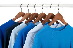 Casual shirts on hangers, different tones of blue Stock Photos