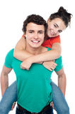 Casual shot of young guy giving piggy ride Stock Image