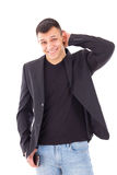 Casual shy man in a black suit jacket and jeans Stock Photography