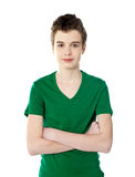 Casual smart boy posing with his arms crossed. Young boy in green t-shirt posing with confidence Royalty Free Stock Photography
