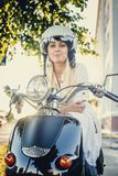 Casual smiling blond woman in moto helmet. Posing on scooter on nature background Royalty Free Stock Image