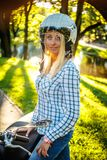 Casual smiling blond woman in moto helmet. Posing on scooter on nature background Royalty Free Stock Photo